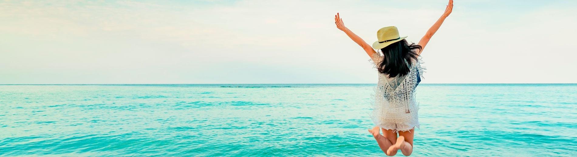 Pessoa com as mãos para cima na praia